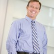 Businessman standing indoors smiling — Stock Photo #4772072