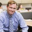 Businessman in cubicle smiling — Foto Stock