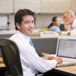 Businessman in cubicle with laptop smiling — 图库照片