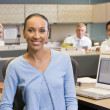 Businesswoman in cubicle smiling — Stock Photo