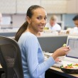 Photo: Businesswoman in cubicle with laptop eating salad