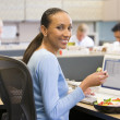 Businesswoman in cubicle with laptop eating salad — Stock Photo