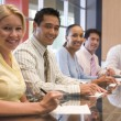 Five businesspeople in boardroom smiling — Stock Photo #4772099
