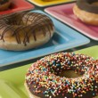 Selection Of Ring Doughnuts On A Different Coloured Plates — Stock Photo