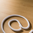 Telephone Cord Making &#039;At&#039; Symbol - Stock Photo