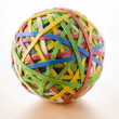 Rubber Band Ball Sitting On Desk - Stock Photo