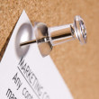 Close Up Of Thumbtack In Bulletin Board - Stock Photo