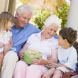 Grandparents with grandchildren on patio with gift smiling — Stock Photo
