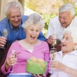 Two couples on patio with champagne and gift smiling - Foto Stock