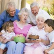 Stock Photo: Grandparents and grandchildren on patio with cake and gift smili