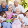 Grandparents and grandchildren on patio with cake and gift smili — Stock Photo #4778078