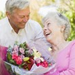 Husband giving wife flowers outdoors smiling - Stock Photo