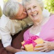 Husband giving wife gift on patio kissing her and smiling — Stock Photo