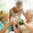 Three women in living room drinking champagne and smiling — Stock Photo
