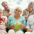 Five friends with champagne and gifts in living room smiling - Stock Photo