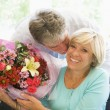 Husband giving wife flowers kissing and smiling - Stock Photo