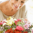 Woman with flowers smiling — Foto de Stock