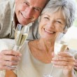 Couple in living room drinking champagne and smiling - Stock Photo