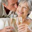 Couple in living room toasting champagne kissing and smiling - Stock Photo