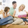 Family in living room with mother receiving gift and smiling — Stock Photo #4778106