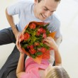 Husband giving wife flowers and smiling — Stock Photo #4778108