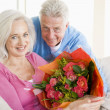 Husband and wife holding flowers and smiling — Stock fotografie