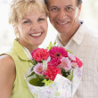 Husband and wife holding flowers and smiling — Stock Photo #4778117