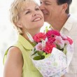 Husband and wife holding flowers kissing and smiling - Foto Stock
