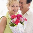 Husband and wife holding flowers and smiling — Stock Photo #4778119