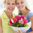 Stock Photo: Granddaughter and grandmother holding flowers and smiling