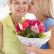Granddaughter kissing grandmother on cheek holding flowers and s — Stock Photo #4778121