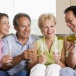 Two couples in living room drinking champagne and smiling — ストック写真