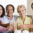Two couples in living room drinking champagne and smiling — Stock Photo