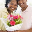 Husband and wife holding flowers smiling - Stock Photo