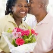 Husband and wife holding flowers kissing and smiling - Stock Photo
