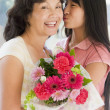 Granddaughter kissing grandmother on cheek holding flowers and s — Stock Photo