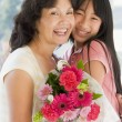Granddaughter and grandmother holding flowers and smiling — Stock Photo #4778157