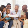 Family in living room smiling with young boy blowing out candles — Stock Photo #4778169
