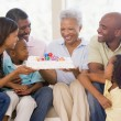 Family in living room with cake smiling — Stock Photo #4778170