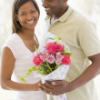 Stock Photo: Husband and wife holding flowers and smiling
