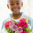 Young boy holding flowers smiling