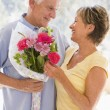 Husband giving wife flowers and smiling - Stock Photo