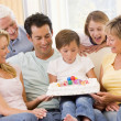 Family in living room smiling with young boy blowing out candles - Stock Photo
