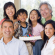 Family in living room with cake smiling - Stock Photo