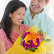 Husband and wife holding flowers and smiling — Stock Photo