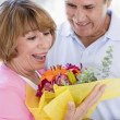 Husband and wife holding flowers and smiling - Stock Photo