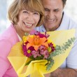 Royalty-Free Stock Photo: Husband and wife holding flowers and smiling