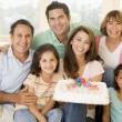 Family in living room with cake smiling — Stock Photo