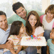 Family in living room with cake smiling - Стоковая фотография