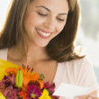 Woman holding flowers and reading note smiling — Stock Photo #4778216